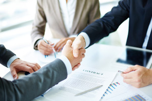 Image of business partners handshaking over business objects on